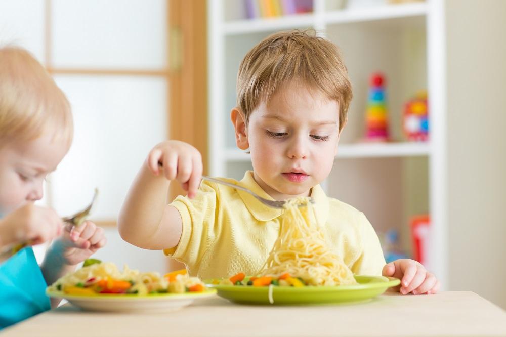 child eating vegetables on noodles