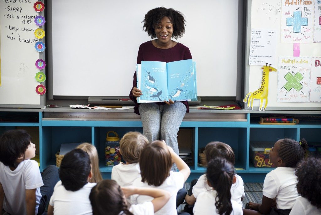 teacher reading a book to her class
