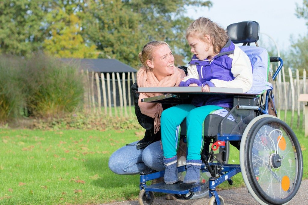 mother kneeling beside her daughter in wheelchair with disability