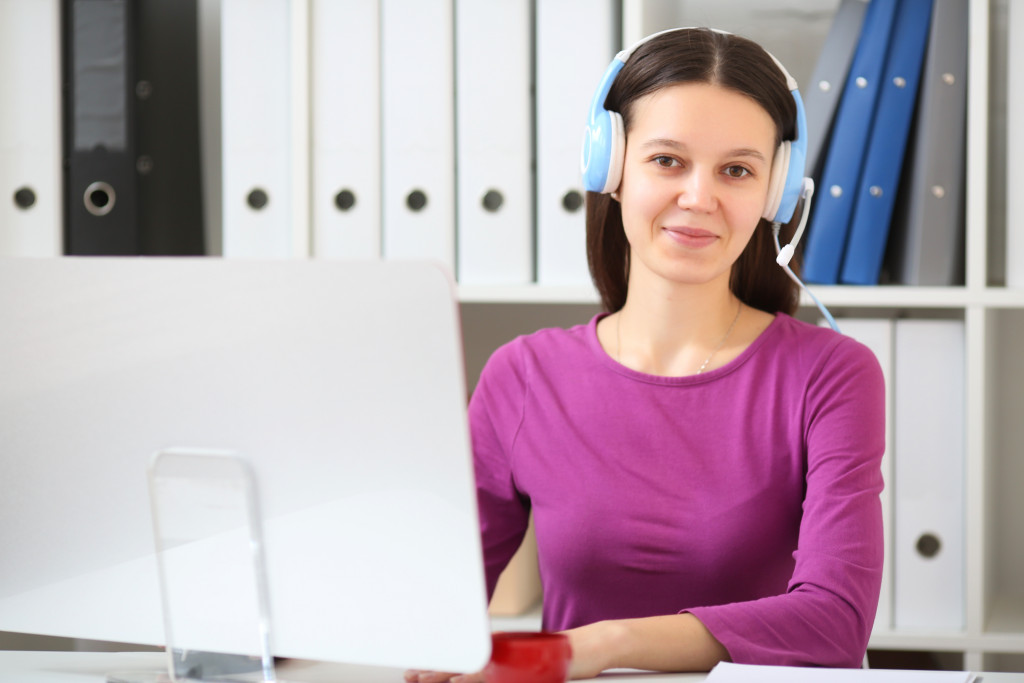 woman infront of desktop with headphones