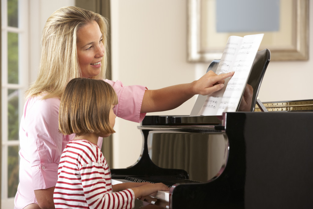 mother teaching her daughter how to play piano